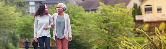 masked mother and daughter walking along paved trail in park