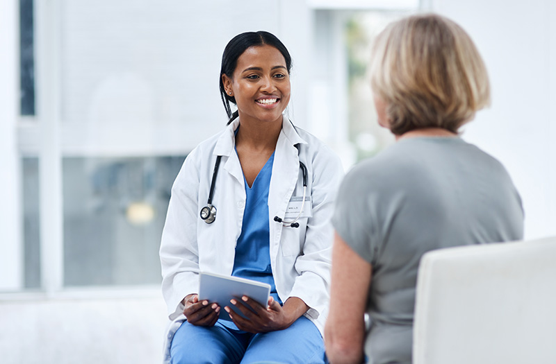 Physician talking with patient while using EHR