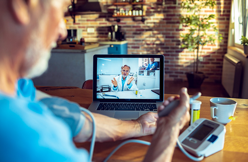 Physician using telehealth with patient checking blood pressure