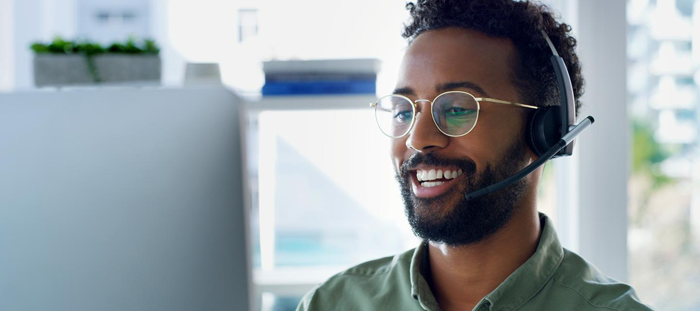 African-American Male with headset while smiling at laptop screen