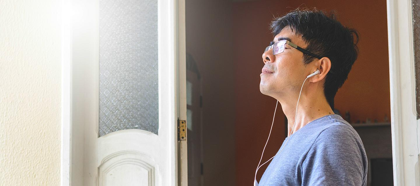 man relaxing wearing ear buds with his eyes closed