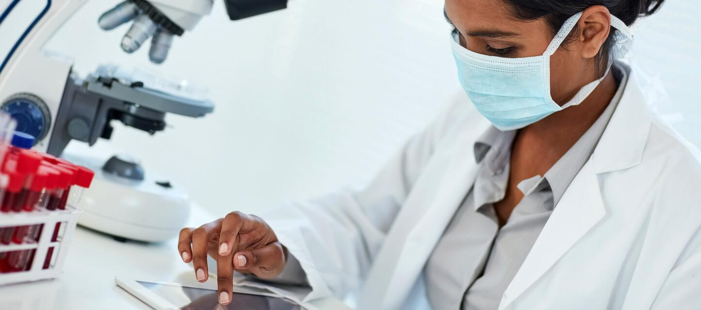 female doctor wearing protective face mask checking blood results on tablet computer